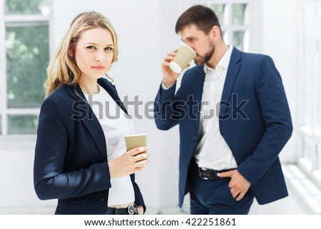 Young colleagues having coffee break in office - stock photo