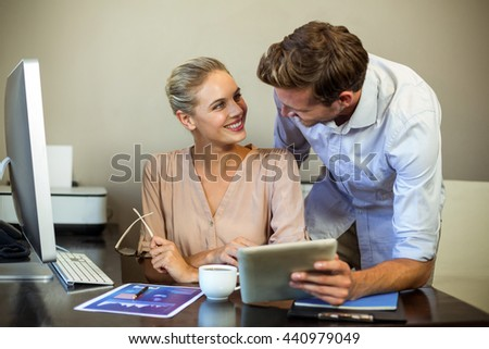 Young colleagues looking at each other while using digital tablet at desk in office - stock photo