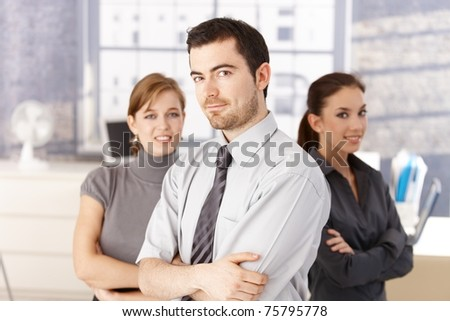 Young colleagues, one man, two women standing in bright office arms crossed, smiling.? - stock photo