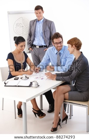 Young colleagues teamworking in meetingroom, smiling.? - stock photo