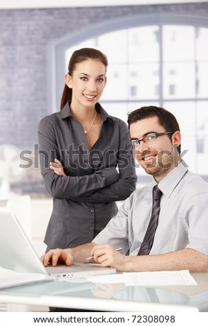 Young colleagues working and smiling in bright office.? - stock photo