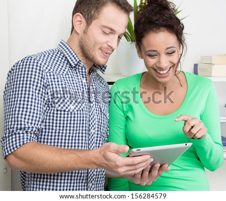 Young colleagues working on tablet in office - stock photo