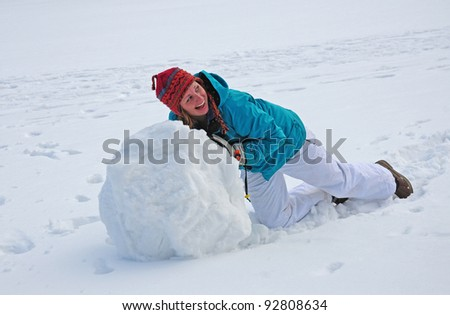 Young college-age woman rolling giant snowball to make snowman - stock photo