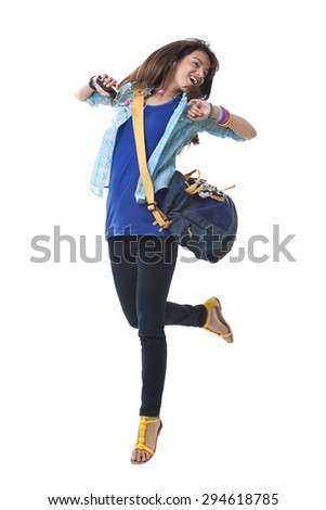 Young college girl dancing while listening music over white background - stock photo