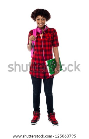 Young college girl posing with backpack, headphones, clipboard, and calculator.