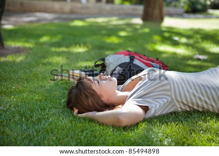Young college student lying down on grass at campus lawn - stock photo