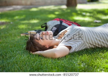 Young college student lying on grass at campus lawn - stock photo