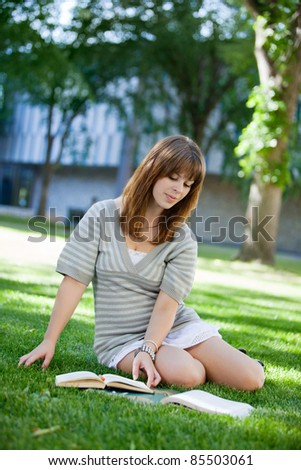 Young college student reading book on campus lawn - stock photo