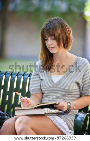 Young college student sitting on campus bench writing