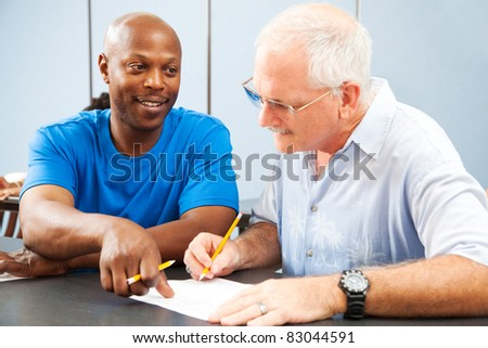 Young college student tutoring an older classmate. - stock photo