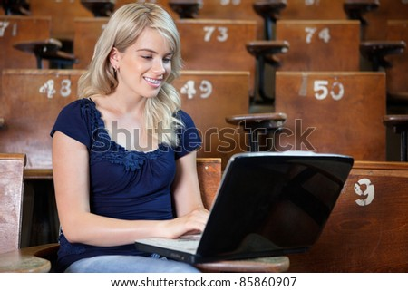 Young college student using laptop at university hall - stock photo