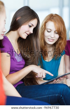Young college students using a tablet computer in class (color toned image) - stock photo