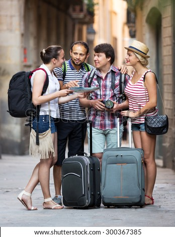Young company of impressed travelers during city walking - stock photo