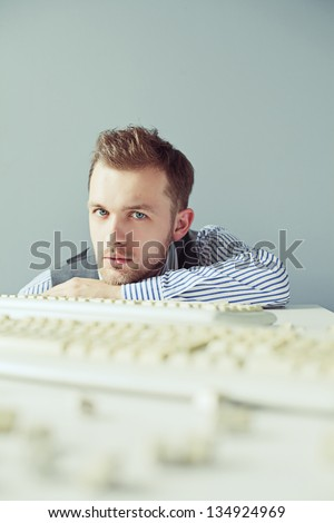 Young computer man looking at camera near table with keyboards - stock photo