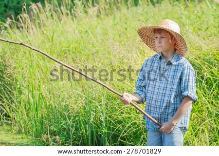 Young concentrated angler boy is watching after handmade fishing rod float on water - stock photo