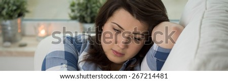 Young concerned woman sitting on psychologist's couch