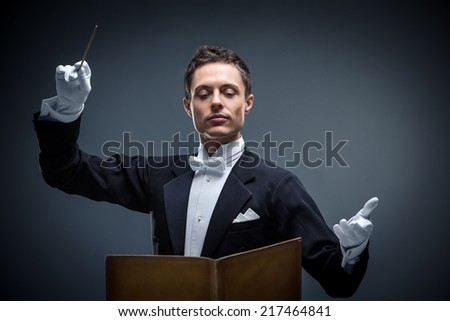 Young conductor in a tuxedo - stock photo