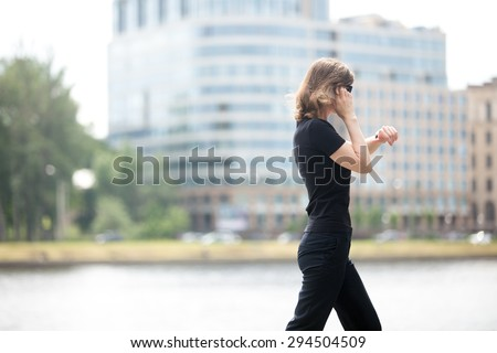 Young confident business woman walking in hurry, looking at watch, talking on mobile phone on the city street in front of blue glass modern office building beside riverbank, profile view - stock photo