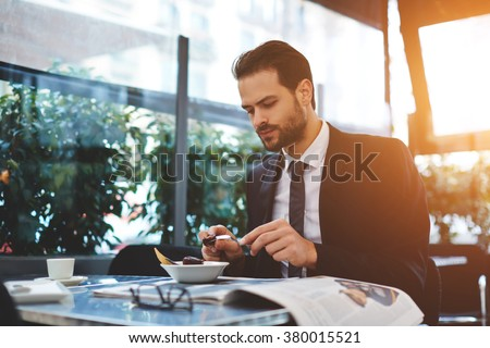 Young confident businessman in luxury suit having breakfast in modern coffee shop during work break, serious male restaurant owner eating tasty dish which was prepared chief cook specially for him  - stock photo