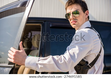 Young confident  businessman  in sunglasses with gun coming out of his luxurious car. - stock photo