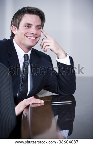 Young confident businessman sitting in boardroom