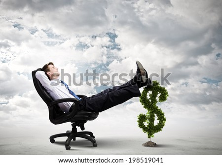 Young confident businessman sitting in chair with legs on dollar sign - stock photo