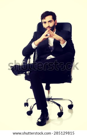 Young confident businessman sitting on a chair. - stock photo