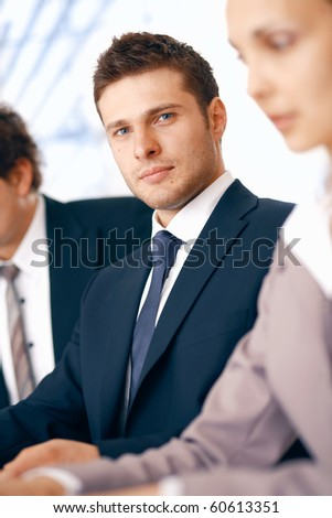 Young confident businessman sitting on the meeting at the office with colleagues. - stock photo