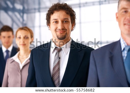 Young confident businessman standing in the row with his colleagues.