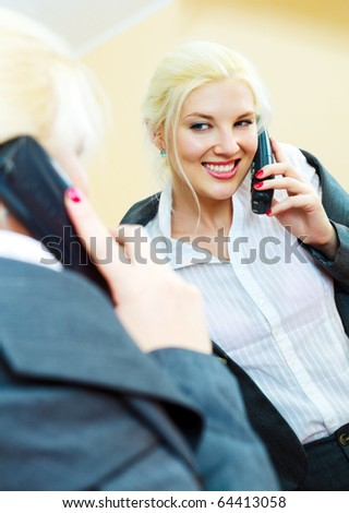 young confident businesswoman talking on the phone and looking at herself in the mirror