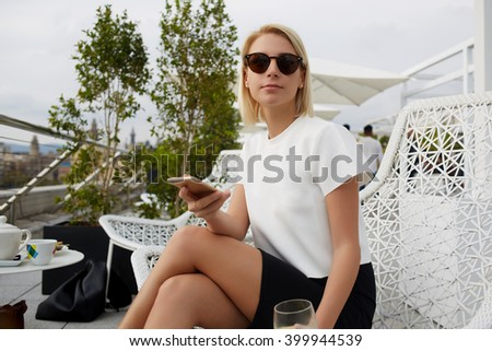 Young confident businesswoman with mobile phone in hands is waiting international partners in coffee shop. Modern female in fashionable sunglasses is using cell telephone during rest in cafe outdoors