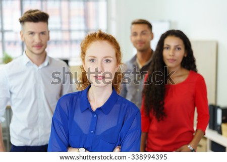 young, confident businesswoman with team in background - stock photo