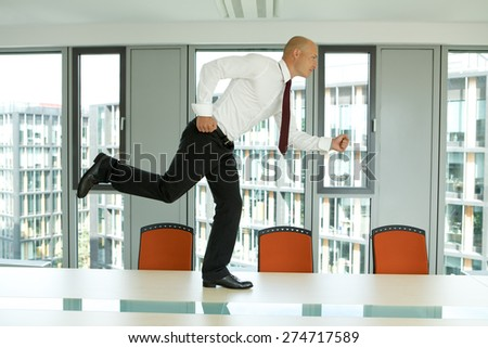 young confident caucasian businessman running on the office table - stock photo