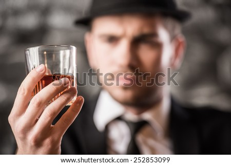 Young, confident, gangster man is drinking a whisky. - stock photo