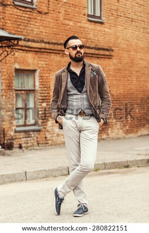 Young confident hipster man with beard in glasses posing on the street in old town. Cute man wearing a vest, black shirt and light trousers. Man keeps hands in pockets and looking forward - stock photo