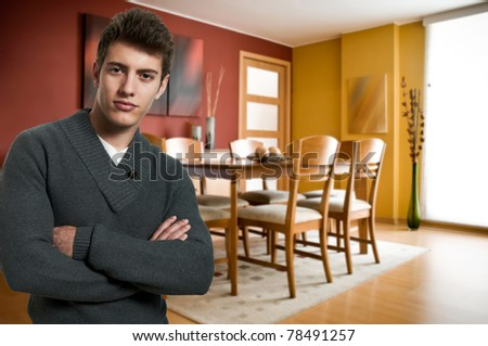 Young confident man at his apartment - stock photo