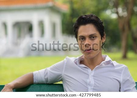 Young confident man close up portrait in Lumpini Park. Bangkok, Thailand. - stock photo
