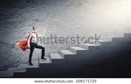 Young confident man in mask and cape walking on ladder - stock photo