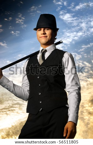 Young confident man in top hat and cane against beautiful sky background - stock photo
