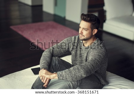Young confident man looking away at home in vintage style - stock photo