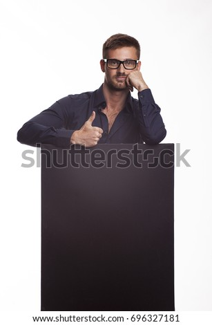 Young confident man portrait of a confident businessman showing presentation, pointing paper placard gray background. Ideal for banners, registration forms, presentation, landings, presenting concept.
