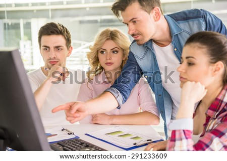Young confident man presenting new business concept to colleagues at meeting room. - stock photo