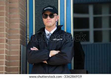 Young Confident Security Guard Standing Arm Crossed - stock photo