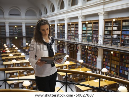 Young confident student standing at handrail upstairs in old university library reading a book. - stock photo
