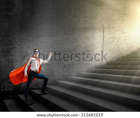 Young confident superman in mask and cape walking on ladder - stock photo