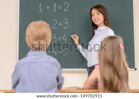 Young confident teacher. Confident young teacher standing near the blackboard and smiling while pupils sitting at desk on foreground - stock photo