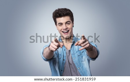 Young confident teenager guy smiling and pointing at camera - stock photo
