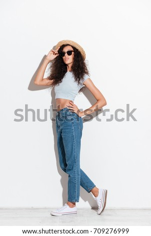 Young confident woman in hat and sunglasses posing isolated over white