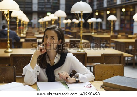 Young confident woman sitting at desk in old university library with books and note pad. - stock photo
