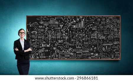 Young confident woman wearing glasses standing near blackboard